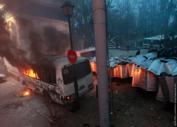 A police van burns after being attacked by Pro-European integration protesters during a rally near government administration buildings in Kiev